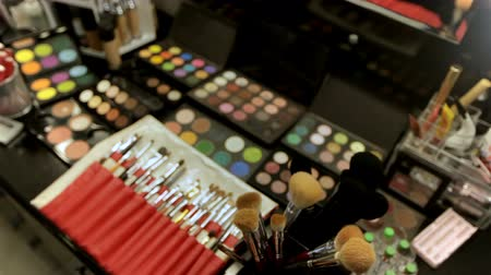 változatos : Professional cosmetics makeup artist on the table in the studio. Multicolored lipstick, shadows and a variety of cosmetic brushes Stock mozgókép