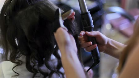relance : The dark-haired young woman twisting her hair into curls in hairdressers close up. Vídeos