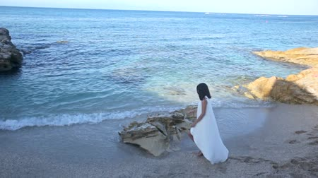aristocrático : Beautiful woman in a long white dress on a seashore Vídeos