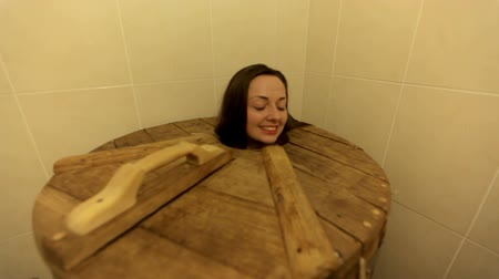 Young woman is in cedar barrel in spa salon indoors.