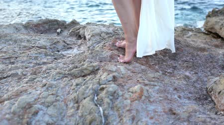 Beautiful girl in white dress is standing on the stones by the sea. Greece Stock mozgókép