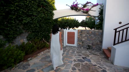 girl comes out of a beautiful house by the sea. Greece