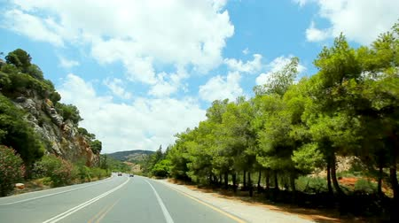 POV vehicle driving across mediterranean green nature, remote countryside, blue sky with white clouds Stock mozgókép
