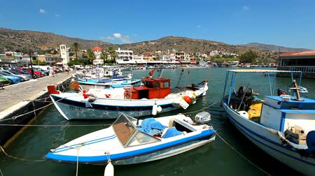 Greece. Beautiful sea coast. Ships and boats in the harbor. People walk along the embankment.
