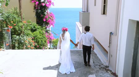 Wedding day. bride and groom go to the sea on a beautiful street with flowers.