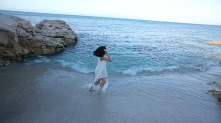 брюнет : beautiful girl in a white dress on the seashore enjoys the sea. Greece