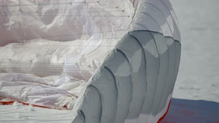 parachuting : preparation for paragliding competition. parachute lies on the snow.