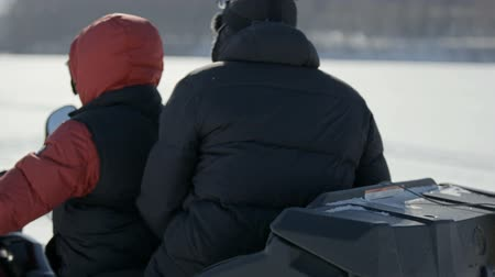 ártico : Winter fun. A trip on a snowmobile. Two guys are riding a snowmobile over frozen lake ice Stock Footage