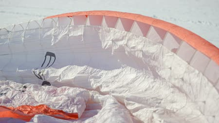 parachuting : paragliding competition. parachute lies on the snow.