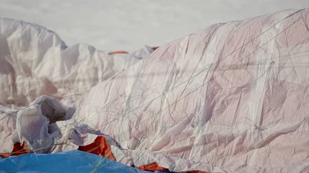 padák : paragliding competition. parachute lies on the snow.
