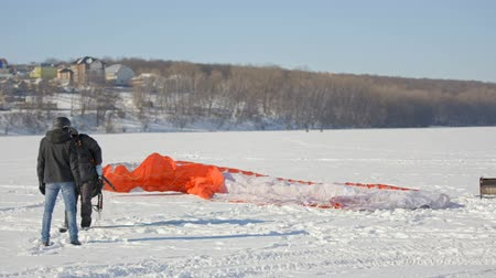 szybowiec : Paragliding landing preparation for paragliding competition. parachute lies on the snow. Wideo
