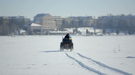 traço : Winter fun. A trip on a snowmobile. Two guys are riding a snowmobile over frozen lake ice Vídeos