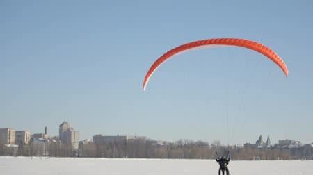 parachuting : Pilots of the paraglider landed on a frozen lake near the city park