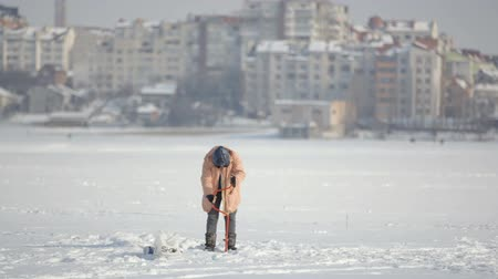 fisher : Fishermen on ice on a frozen lake near the city park Stock Footage