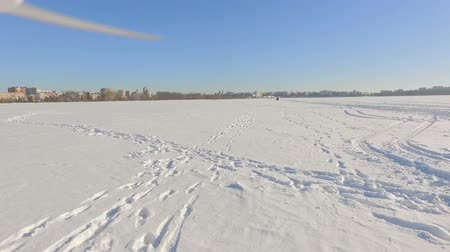 white out : drone flies over a frozen lake near a city park in the background of a winter city in clear sunny weather