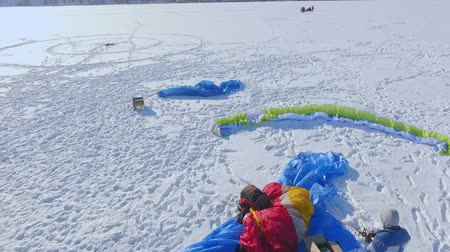 parachuting : aerial view. Competitions pilots paragliding on a frozen lake near the city park. Stock Footage