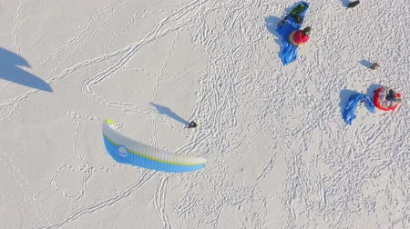 parachuting : aerial view. preparation for winter paragliding competition on a frozen lake near the city park.
