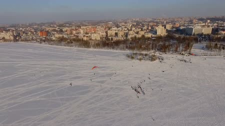 harness : aerial view. Competitions pilots of the paraglider on a frozen lake near the city park.