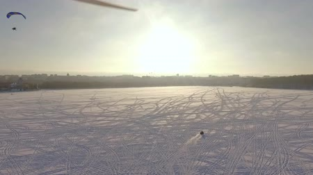 szybowiec : aerial view. Competitions pilots of the paraglider on a frozen lake near the city park at sunset of the day