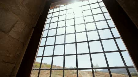 fortress : View of the mountains through a window with a lattice