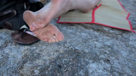 kobiece stopy : funny dirty female feet on a stone beach.