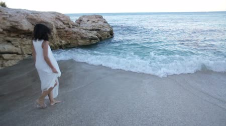 aristocrático : beautiful girl in a white dress on the seashore enjoys the sea. Vídeos