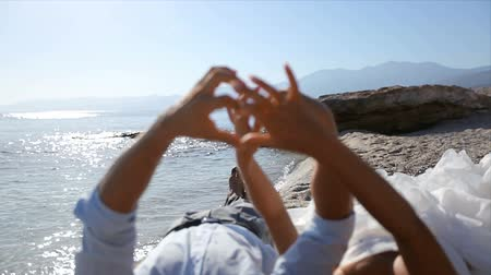 жених : Bride and groom by the sea on their wedding day make a heart out of fingers