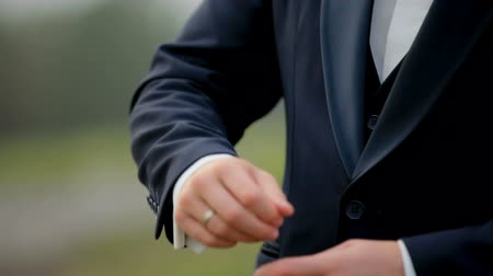 sleeve : A young man in black suit adjusts his cufflinks of white shirt. Indoor. Close-up. Interior. Sunshine. Steady