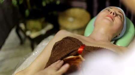 masszírozó : Masseur puts warm chocolate on the girls body for massage Stock mozgókép