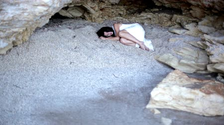 gruta : A frightened girl lies on the sand in a stone grotto