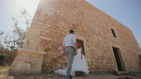taş duvar : Romantic photosession of the bride and groom near the old castle. Stok Video