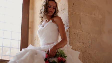 casar : A beautiful bride sits near a window in an old castle
