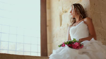 príncipe : A beautiful bride sits near a window in an old castle