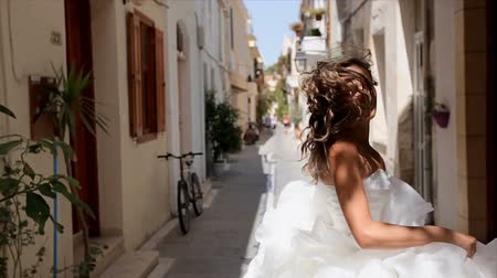да : happy cheerful bride runs along the street of the old city and looks back.