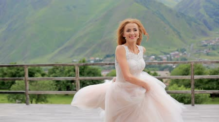 taras : Beautiful red-haired bride dancing against the background of mountains Wideo