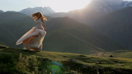 rejoice : Girl in a beautiful dress on a background of mountains and sunset Stock Footage