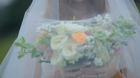 duygusallık : Beautiful bride under a veil with a bouquet of flowers. Mysterious image Stok Video