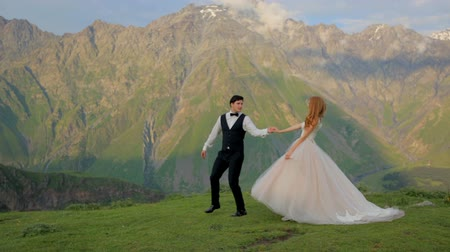 chique : Happy bride and groom in the background of mountains Vídeos