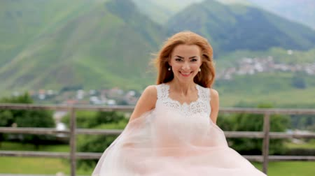 fiancee : Beautiful red-haired bride dancing against the background of mountains Stock Footage
