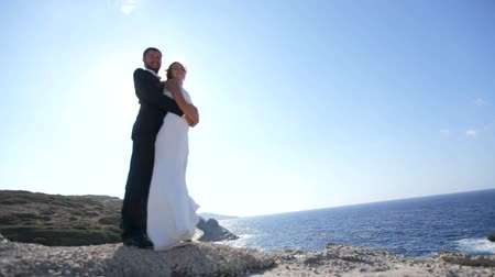 yalınayak : Bride and groom on the seashore on their wedding day. Stok Video