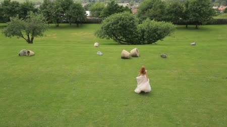Грузия : happy bride is dancing on the green grass against the backdrop of the mountains and orchard Slow motion