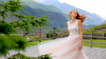 fiancee : Beautiful red-haired bride dancing against the background of mountains. slow motion