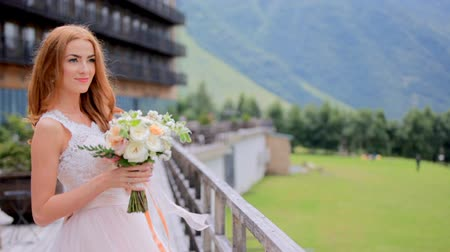 fiancee : Bride blonde relaxing while looking at mountains. Wedding day Stock Footage