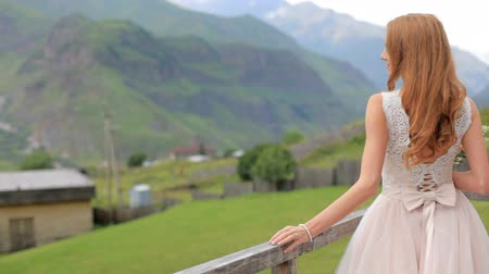 fiancee : Beautiful red-haired bride against the background of mountains