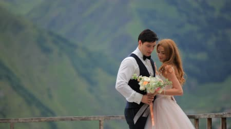 greater : Wedding day. Groom and bride against the background of mountains