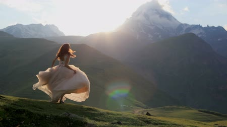 lem : beautiful girl in a chic dress dances in the evening against the backdrop of the mountains and the setting sun Dostupné videozáznamy