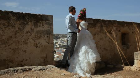 taş duvar : Happy bride and groom kissing on the background of ancient ruins.