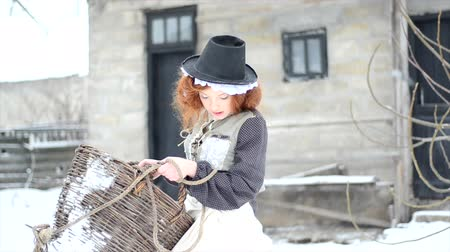 szerény : Pretty Red-haired girl with a large basket walks around the yard of a country house