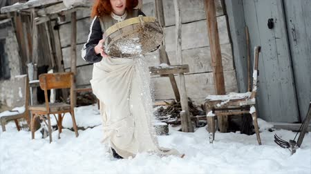 szerény : girl in a fairy-tale dress is standing by the old wooden house and throwing snow Stock mozgókép
