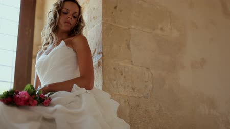kőfal : A beautiful bride sits near a window in an old castle